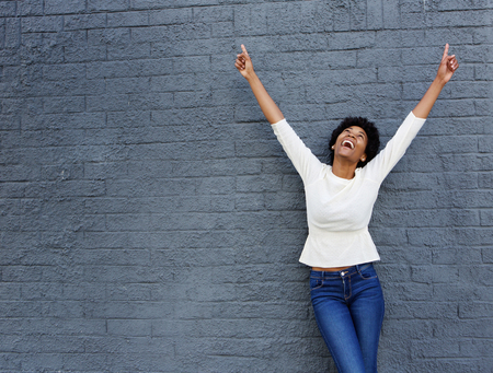 Photo for Portrait of a cheerful african woman with hands raised pointing up - Royalty Free Image