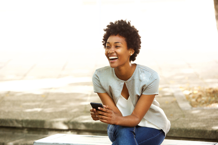 Photo for Portrait of beautiful young african woman smiling while sitting outside on a bench holding mobile phone - Royalty Free Image
