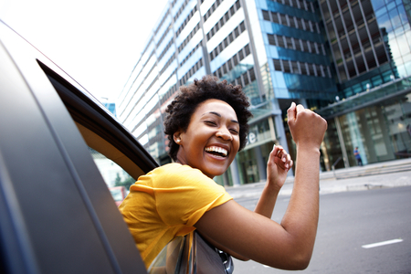 Foto de Portrait of cheerful young african woman looking out the car window with her arms raised - Imagen libre de derechos