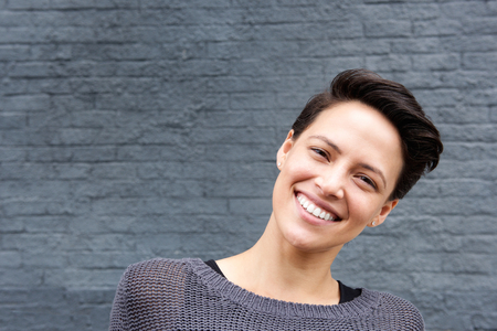 Photo for Close up portrait of a smiling young woman with short hair against gray background - Royalty Free Image