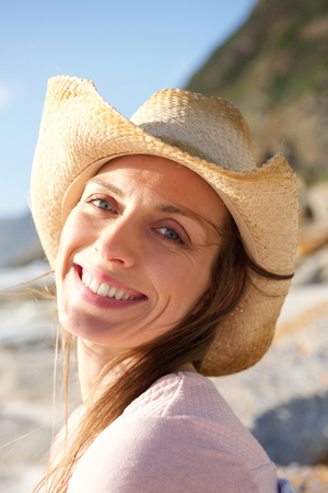 Foto für Close up portrait of a smiling woman with hat at the beach - Lizenzfreies Bild