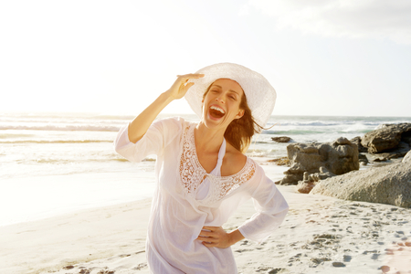 Foto de Portrait of a beautiful carefree woman walking on beach with sun dress and hat - Imagen libre de derechos