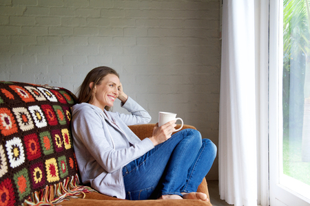 Foto de Portrait of a smiling older woman relaxing at home with cup of tea - Imagen libre de derechos