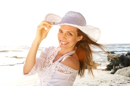 Foto per Close up portrait of a beautiful woman smiling with hat at the beach - Immagine Royalty Free