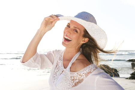 Foto de Close up portrait of an attractive woman laughing with hat at the beach - Imagen libre de derechos