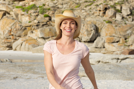 Foto per Portrait of a smiling older woman walking at the beach with hat - Immagine Royalty Free