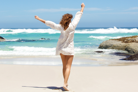 Photo pour Back of young woman with arms raised in the air at the beach - image libre de droit
