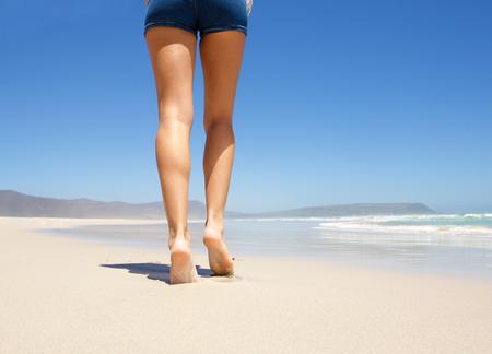 Foto de Female legs walking barefoot on beach from behind - Imagen libre de derechos