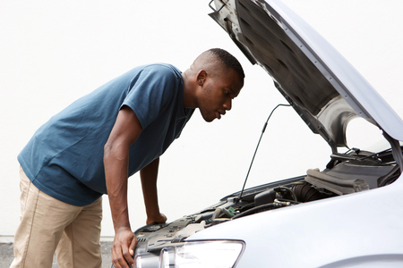 Foto de Side portrait of young african american guy looking under the hood of broken down car - Imagen libre de derechos