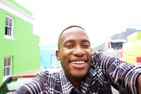 Photo for Close up of happy young man on the city street taking a self portrait - Royalty Free Image