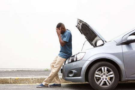 Foto de Full length portrait of upset young african man standing in front of a broken down car parked on the side of a road - Imagen libre de derechos