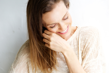 Foto per Close up candid portrait of a woman laughing against white background - Immagine Royalty Free