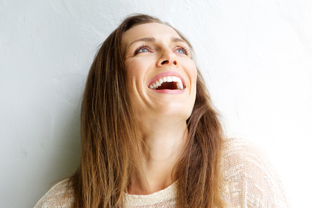 Foto de Close up portrait of a beautiful middle aged woman laughing against white background - Imagen libre de derechos