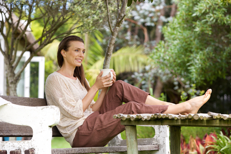 Foto de Portrait of an older woman sitting outside with cup of coffee - Imagen libre de derechos