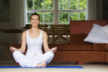 Photo pour Attractive woman sitting on floor at home in yoga position - image libre de droit