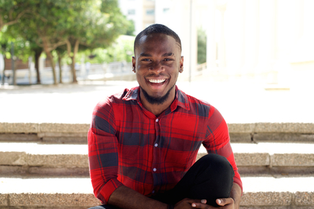 Foto de Close up portrait of smiling young african man sitting outdoors on steps - Imagen libre de derechos