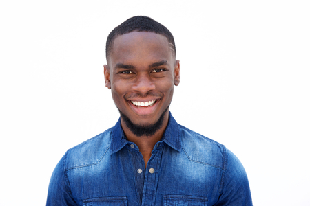Foto de Close up portrait of a smiling young african american man in a denim shirt against white background - Imagen libre de derechos