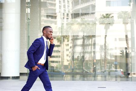 Photo pour Side portrait of a happy young man in suit walking and talking on mobile phone - image libre de droit