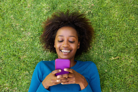 Photo pour Portrait from above of a smiling african woman lying on grass looking at cell phone - image libre de droit
