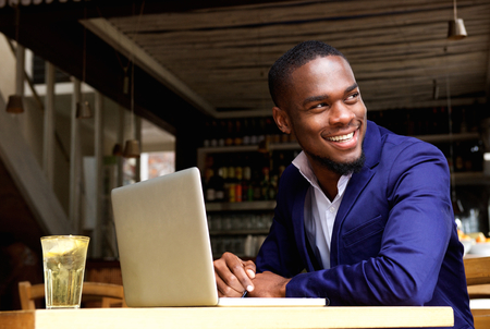 Photo for Portrait of a smiling black businessman with laptop at cafe - Royalty Free Image