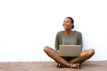 Photo pour Portrait of happy young african american woman sitting on sidewalk with laptop - image libre de droit