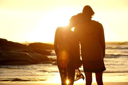 Photo for Portrait from behind of loving couple holding hands at the beach and watching the sunset - Royalty Free Image