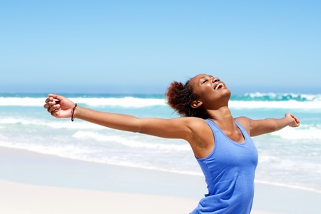 Photo pour Portrait of healthy young african woman standing on the beach with her hands outstretched - image libre de droit