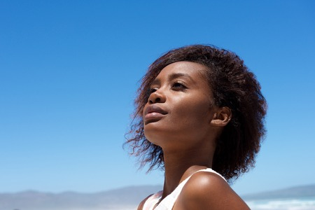 Close up portrait of attractive young african woman looking away against sky outdoors