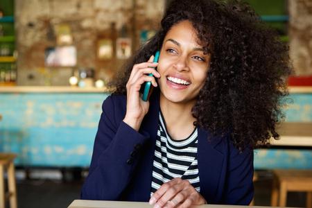 Foto de Close up portrait of laughing young woman talking on cellphone at cafe - Imagen libre de derechos