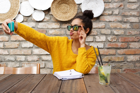 Foto de Portrait of stylish young african woman wearing sunglasses sitting at cafe and taking selfie with her smart phone - Imagen libre de derechos