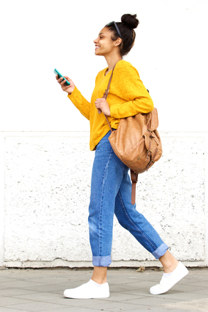 Photo for Full length side portrait of stylish young woman walking with bag and mobile phone - Royalty Free Image