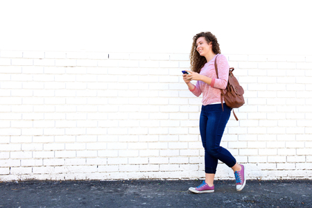 Photo for Portrait of smiling teen girl walking with cellphone and backpack - Royalty Free Image
