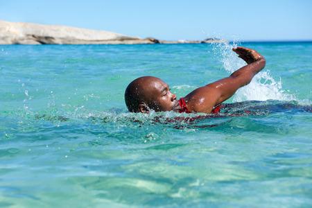 Photo pour Portrait of young african man swimming in sea - image libre de droit