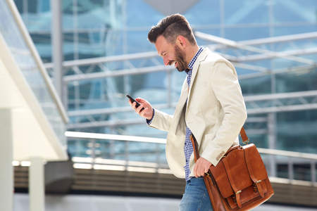 Photo for Side portrait of smiling mature man with bag walking outdoors and reading text message on his cell phone - Royalty Free Image