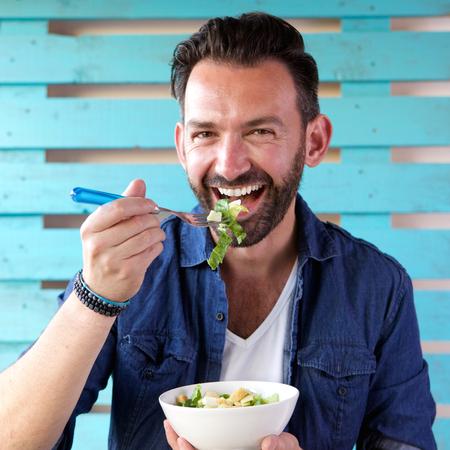Photo pour Close up portrait of cheerful man eating salad from bowl - image libre de droit