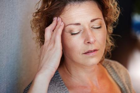 Photo pour Close up portrait of older woman with hand to head in pain - image libre de droit