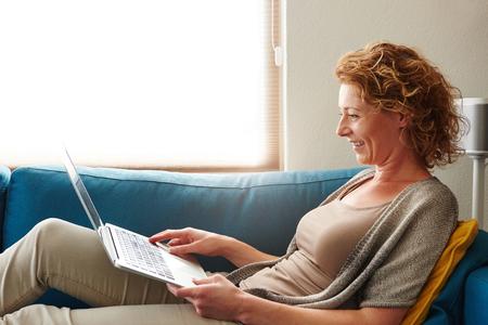 Photo pour Side portrait of woman lying on sofa with laptop smiling - image libre de droit