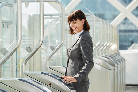 Photo for Portrait of professional business woman walking through platform barrier - Royalty Free Image