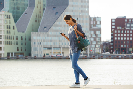 Photo for Full length portrait of happy young woman walking water in city with mobile phone - Royalty Free Image