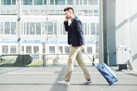 Photo for Full length side portrait of business man walking with luggage on telephone call at station - Royalty Free Image
