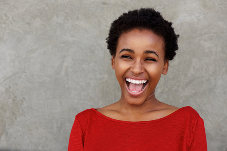 Foto de Portrait of beautiful young black woman laughing with open mouth - Imagen libre de derechos