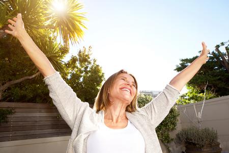 Foto de Happy portrait of smiling older woman with arms outstretched - Imagen libre de derechos