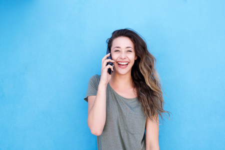 Foto de Front portrait of young laughing woman talking on cellphone against blue background - Imagen libre de derechos