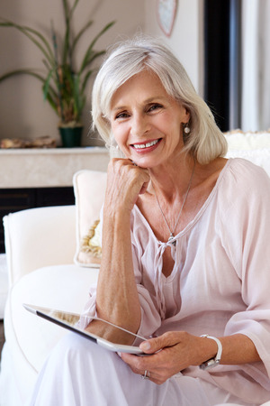 Foto per Portrait of smiling older woman in living room with tablet - Immagine Royalty Free