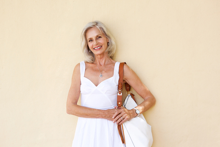 Foto per Portrait of happy older woman standing in white dress with purse - Immagine Royalty Free