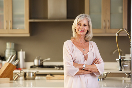 Foto per Portrait of smiling older woman standing in modern kitchen - Immagine Royalty Free