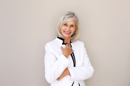 Photo pour Portrait of beautiful older woman smiling and standing by wall - image libre de droit