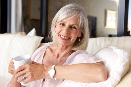 Foto per Close up portrait of older woman sitting on couch with coffee - Immagine Royalty Free