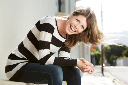 Foto per Portrait of cheerful woman sitting by the street and laughing - Immagine Royalty Free