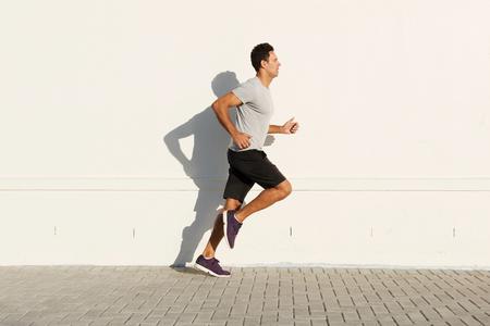 Photo pour Side portrait of middle age man running by white wall - image libre de droit